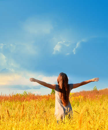 Free happy woman enjoys freedom on sunny meadow. Nature.