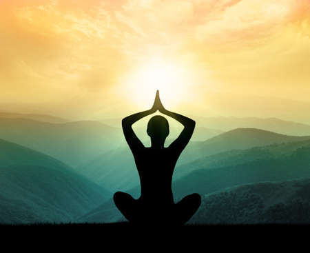 Foto de Yoga and meditation. Silhouette of man in the mountain - Imagen libre de derechos
