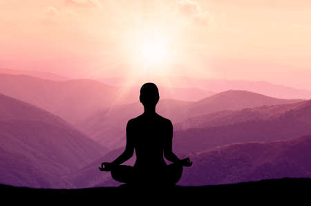 Foto de Yoga silhouette on the mountain in sunrays. the dawn sun - Imagen libre de derechos