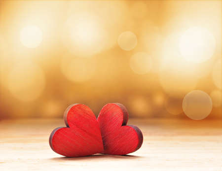 Foto de Close up of two red wooden hearts against defocused lights. - Imagen libre de derechos