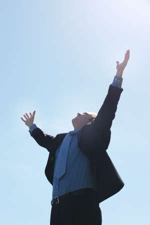Business man raising his hands up to the sky as he is smiling and dressed in a black suit in a blue shirt and tie