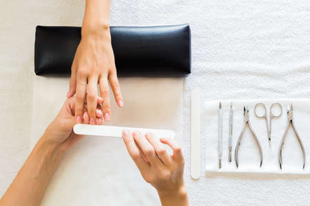 Foto de Beautician performing a manicure in a salon on a lady client filing her nails with a file, view from above of their hands and tools - Imagen libre de derechos