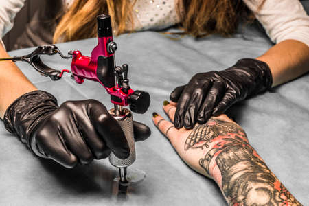 Photo pour Tattoo artist takes an orange paint for black and red tattoo which draws for a girl. Master works in a professional salon with pink tattoo machine on a blue mat and in sterile  black gloves. - image libre de droit