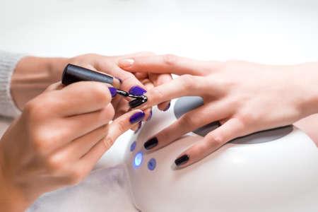 Foto de Closeup manicurist applies nail gel polish on middle finger. Girl client holds hand on the client on Uv lamp. Beautician gently manicured service. - Imagen libre de derechos