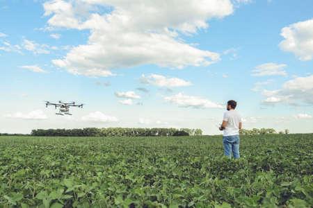 Foto de Technician farmer use wifi computer control agriculture drone on green field. Agriculture drone on the green field. - Imagen libre de derechos