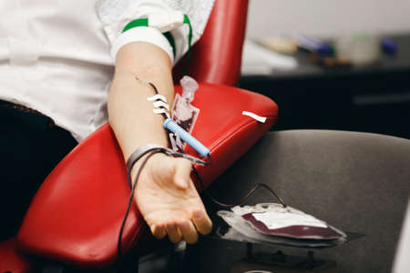 Foto de The donor blood donates blood in the clinic on a special chair. Blood sampling procedure for blood bank - Imagen libre de derechos