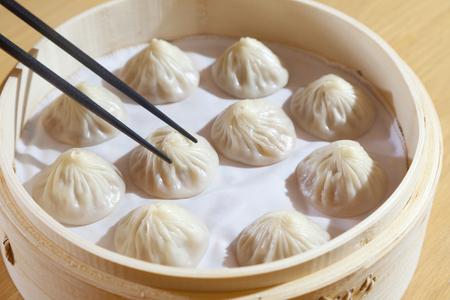 Foto de Chinese steamed pork bun, selective focus on piece held in chopsticks - Imagen libre de derechos