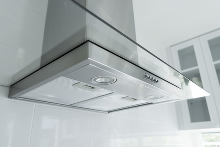 Photo for Metal cooker hood extractor fan with spotlight in luxury kitchen. - Royalty Free Image