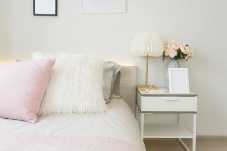 Photo for Pink and blue blanket with creative pillows on bed in colorful kids room with white side table and lamp. - Royalty Free Image