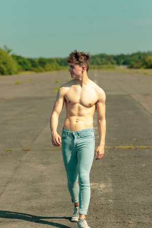 Photo pour Young adult male walking forward shirtless on a warm summer's day - image libre de droit