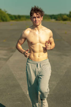 Photo for A young caucasian adult male jogging shirtless on a warm summer's day - Royalty Free Image