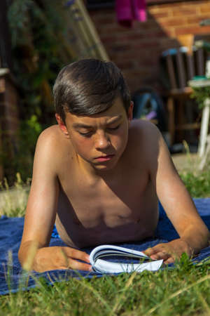 Photo for Teenage boy reading a book while sunbathing in a garden - Royalty Free Image