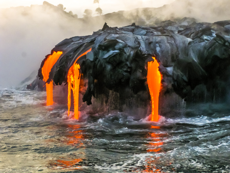 Foto de Sea view of Kilauea Volcano in Big Island, Hawaii, United States. A restless volcano that has been in business since 1983. Shot taken at sunset when the lava glows in the dark as jumps into the sea. - Imagen libre de derechos