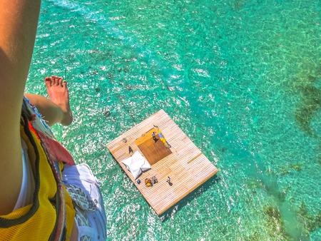 Foto de Aerial closeup view of a woman parasailing. Below, the landing platform on the spectacular blue sea of Deer Island, east coast of Mauritius, Indian Ocean. - Imagen libre de derechos