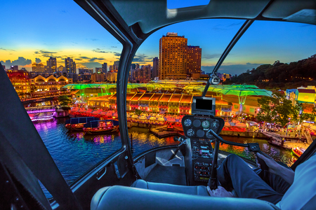 Foto de Helicopter cockpit interior flying on aerial skyline of Clarke Quay and riverside area at sunset in Singapore, Southeast Asia. Waterfront skyline on Singapore River. Popular nightlife attraction. - Imagen libre de derechos