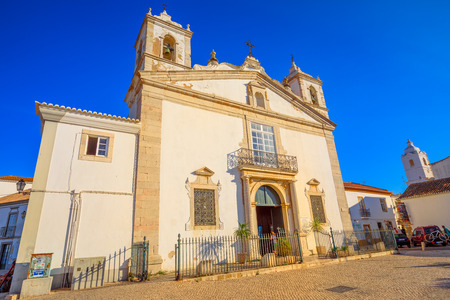 Photo pour Lagos, Portugal - June 8, 2018: perspective view of historic Santa Maria Church in the old town of Lagos, Algarve, in Infante Dom Henrique square. Blue sky in sunny day. - image libre de droit
