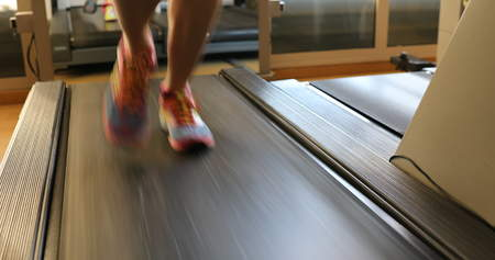 Foto de Running shoes training. Woman feet in colorful shoes running on treadmill machine indoor. Fitness center training. Healthy lifestyle concept. - Imagen libre de derechos
