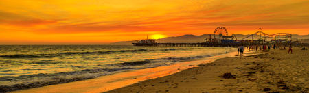 Foto de Scenic landscape of iconic Santa Monica Pier at orange sunset sky from the beach on Paficif Ocean. Santa Monica Historic Landmark, California, USA. Wide banner panorama. - Imagen libre de derechos