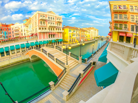 Foto de Wide angle view of panoramic bridge in Venice at Qanat Quartier in the Pearl, Persian Gulf, Middle East at sunset. Aerial view picturesque and luxurious district icon of Doha, Qatar, in venetian style - Imagen libre de derechos