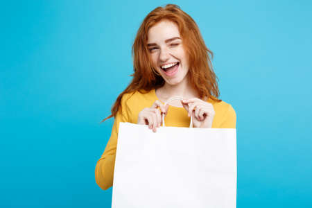 Foto für Shopping Concept - Close up Portrait young beautiful attractive redhair girl smiling looking at camera with white shopping bag. Blue Pastel Background. Copy space. - Lizenzfreies Bild