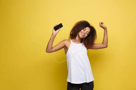 Foto de Lifestyle Concept - Portrait of beautiful African American woman joyful listening to music on mobile phone. Yellow pastel studio background. Copy Space. - Imagen libre de derechos