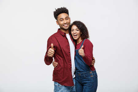Foto de Portrait of attractive African american couple showing thumb up over white studio background. - Imagen libre de derechos