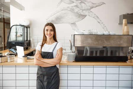 Foto de Coffee Business owner Concept - Portrait of happy attractive young beautiful caucasian barista in apron smiling at camera in coffee shop counter. - Imagen libre de derechos