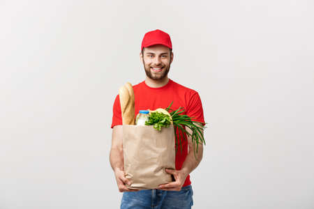 Photo pour Delivery Concept - Handsome Cacasian delivery man carrying package bag of grocery food and drink from store. Isolated on Grey studio Background. Copy Space. - image libre de droit