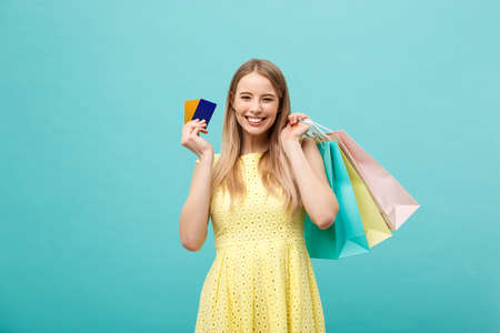 Photo pour Shopping and Lifestyle Concept: Beautiful young girl with credit card and colorful shopping bags. Isolated on blue background - image libre de droit
