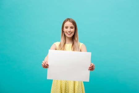 Foto de Lifestyle Concept: young beautiful girl smiling and holding a blank sheet of paper, dressed in yellow, isolated on pastel blue background - Imagen libre de derechos