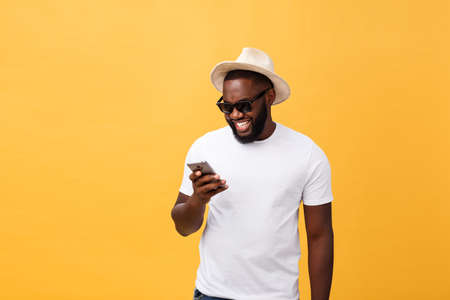 Foto de Cheerful African American man in white shirt using mobile phone application. happy dark skinned hipster guy read news from social network in mobile phone. - Imagen libre de derechos