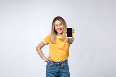 Photo pour Close up portrait of a smiling asian woman showing blank screen mobile phone while standing isolated over gray background. - image libre de droit
