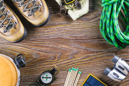 Photo pour Hiking or travel equipment with boots, compass, binoculars, matches on wooden background. Active lifestyle concept. Top view - image libre de droit