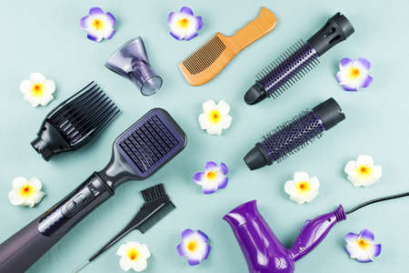 Photo for Hairdressing tools with flowers on blue wooden background - Royalty Free Image