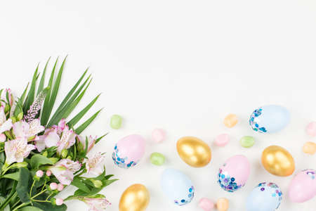 Photo for Festive Easter background with decorated eggs, flowers, candy and ribbons in pastel colors on white background - Royalty Free Image