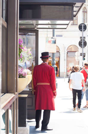 Photo pour VIENNA, AUSTRIA - MAY, 22: Porter in red uniform next to the hotel door waiting guests on May 22, 2018 - image libre de droit