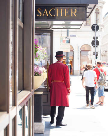 Photo pour VIENNA, AUSTRIA - MAY, 22: Porter in red uniform next to the sacher hotel door waiting guests on May 22, 2018 - image libre de droit
