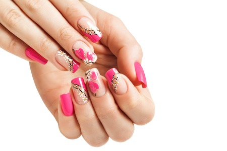 Foto de Nail art manicure, with a pattern of flowers and hearts. Isolated. - Imagen libre de derechos