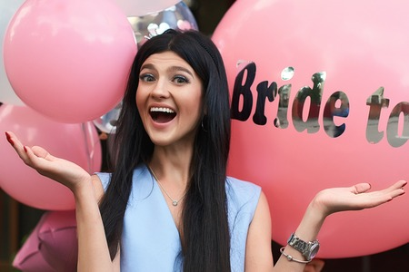 Foto de Happy young beautiful brunette bride to be with dark hair and silver crown smiling and spreading out her hands in joy on bachelorette pink party balloon background - Imagen libre de derechos