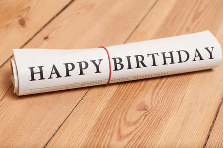 Photo pour happy birthday newspaper on wooden floor - image libre de droit