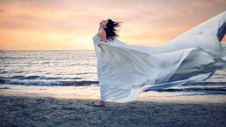 Photo for Beautiful young woman in white dress on a stormy beach - Royalty Free Image