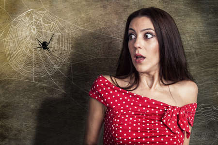 Photo for Beautiful woman is shocked to a spider next to her face - Royalty Free Image