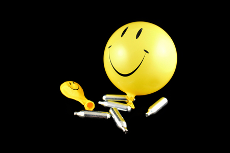 Photo pour Laughing gas balloons stock images. Happy emoji balloon stock images. Smiley inflatable balloon isolated on a black background. Laughing party balloon. Laughing gas bombs stock images - image libre de droit