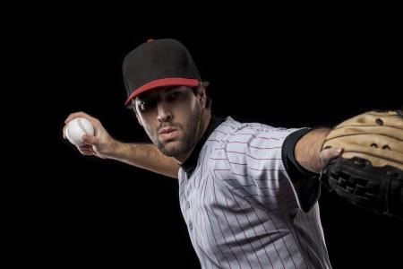 Baseball Player pitching a ball on a black background. Studio Shot.
