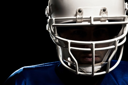Football Player with number on a blue uniform and a ball in the hand  Studio shot
