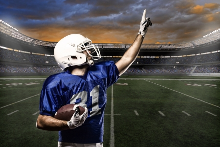 Football Player with a blue uniform celebrating with the fans.