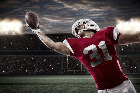 Football Player with a red uniform catching a ball on a stadium..