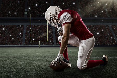 Photo pour Football Player with a red uniform on his knees, on a Stadium. - image libre de droit