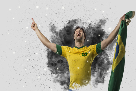 Foto de Brazilian soccer player coming out of a blast of smoke. celebrating. - Imagen libre de derechos
