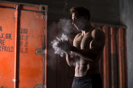 Athlete with a naked torso clapping rubs talc before performing the exercises. Studio shot.